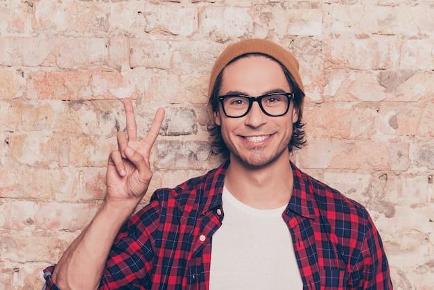Giovane hipster in piedi vicino al muro di mattoni e mostrando due dita