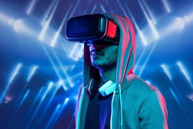 Giovane hipster con stoppie immerso nella realtà virtuale che indossa la felpa con cappuccio guardando film in 3d su sfondo blu luminoso