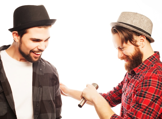 Hipsters: due giovani che cantano con il microfono. isolato su bianco.