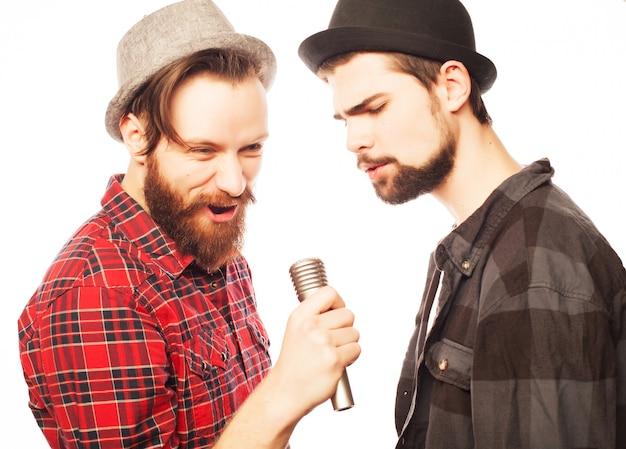 Hipsters: due giovani uomini che cantano con il microfono. isolato su bianco. Foto Premium