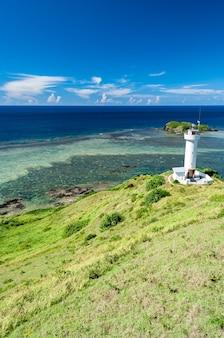 Faro di hirakubo circondato da erba verde cielo blu profondo oceano blu pieno di barriere coralline