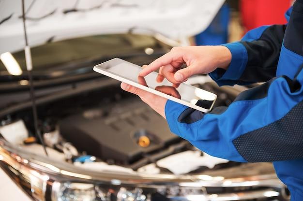 Il suo aiutante al lavoro. primo piano di un uomo in uniforme che lavora su una tavoletta digitale mentre si trova davanti al cofano dell'auto in officina