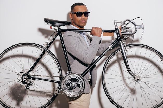 Nel suo stile. fiducioso giovane africano in occhiali da sole che porta la sua bicicletta in stile retrò