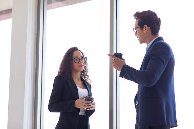Uomo d'affari ispanico e imprenditrice che riposano parlando e bevono caffè nel moderno ufficio a casa. team professionale di uomini d'affari di successo.