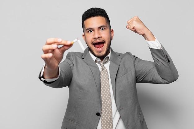 Uomo d'affari ispanico che celebra con successo una vittoria. smettere di fumare concetto