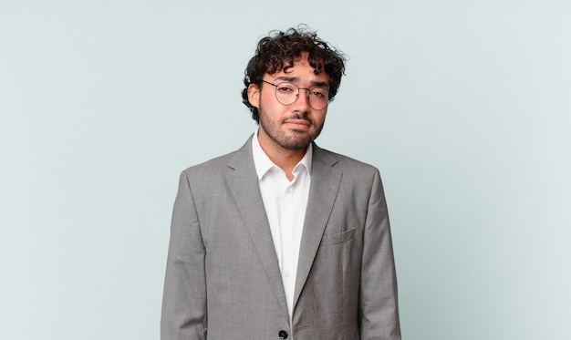Uomo d'affari ispanico che si sente triste e piagnucoloso con uno sguardo infelice, piange con un atteggiamento negativo e frustrato