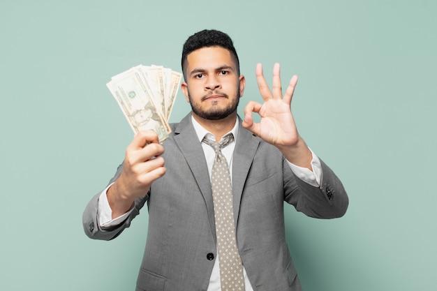 Espressione felice dell'uomo d'affari ispanico e che tiene banconote in dollari