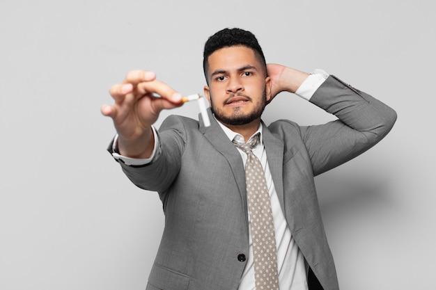 Espressione spaventata dell'uomo d'affari ispanico. smettere di fumare concetto