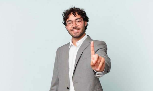 Uomo d'affari ispanico che sorride con orgoglio e sicurezza facendo posare trionfalmente il numero uno, sentendosi come un leader