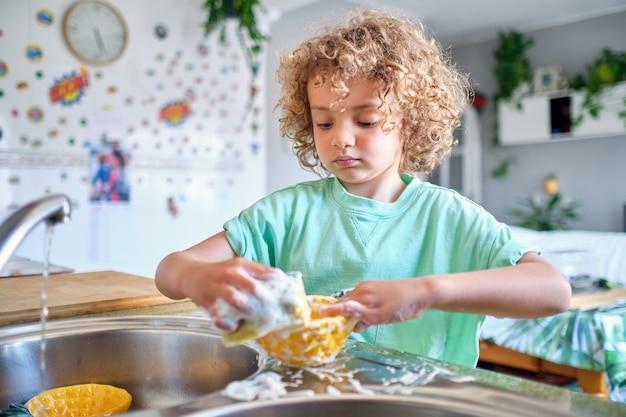 Bambino ispanico che lava i piatti del pranzo con acqua e sapone