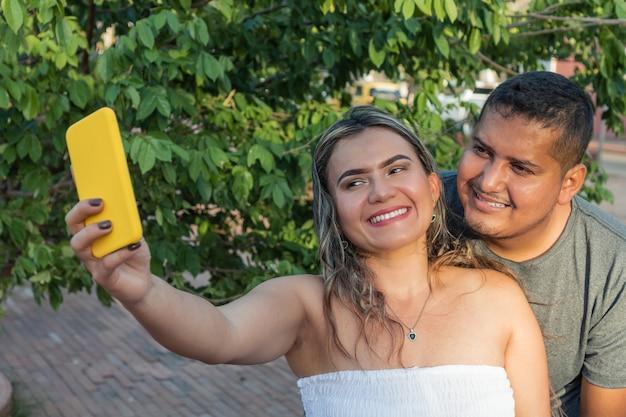 Coppia ispanica nel parco. coppia felice che scatta foto con il telefono.