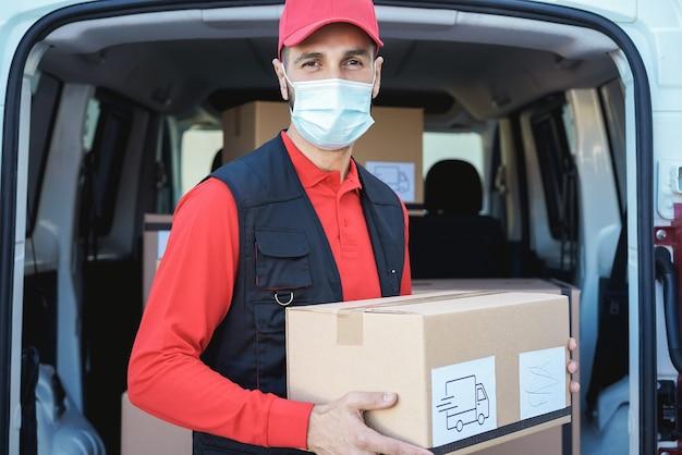 Uomo di consegna ispanico che indossa una maschera di sicurezza per la prevenzione del coronavirus - focus sul viso
