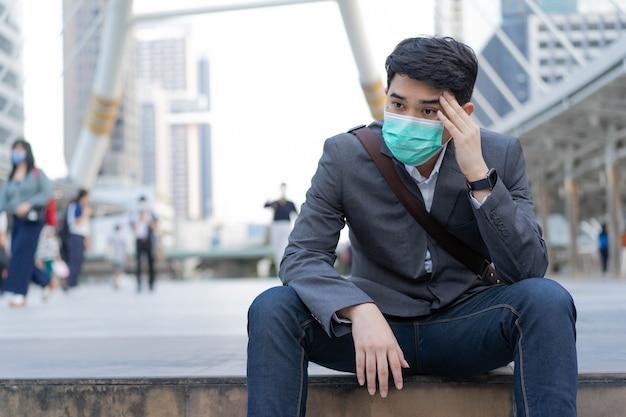 L'impiegato ispanico indossa la maschera mentre è seduto fuori dall'edificio con la sensazione di essere esausto