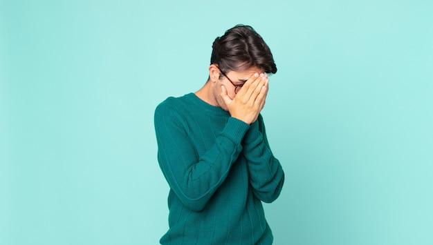 Bell'uomo ispanico che copre gli occhi con le mani con uno sguardo triste e frustrato di disperazione, pianto, vista laterale
