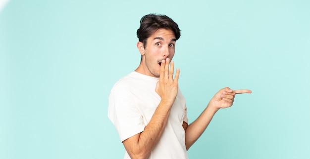 Bell'uomo ispanico che si sente felice, scioccato e sorpreso, coprendo la bocca con la mano e indicando lo spazio laterale della copia