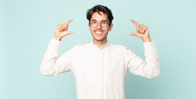 Ispanico bell'uomo che incornicia o delinea il proprio sorriso con entrambe le mani, guardando positivo e felice, concetto di benessere