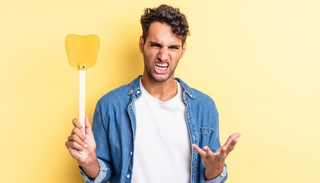 Bell'uomo ispanico che sembra arrabbiato, infastidito e frustrato. uccide il concetto di mosche