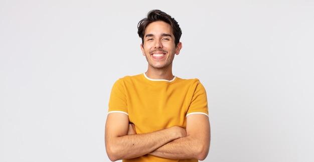 Un bell'uomo ispanico che sembra un uomo d'azione felice, orgoglioso e soddisfatto che sorride con le braccia incrociate