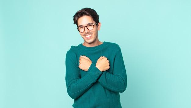 Bell'uomo ispanico che sorride allegramente e festeggia, con i pugni serrati e le braccia incrociate, sentendosi felice e positivo
