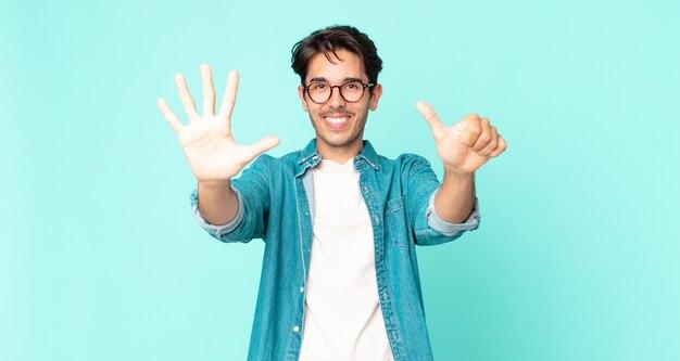 Ispanico bell'uomo sorridente e dall'aspetto amichevole, mostrando il numero sei o il sesto con la mano in avanti, conto alla rovescia