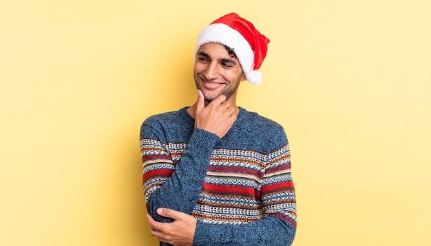 Uomo bello ispanico che sorride con un'espressione felice e sicura con la mano sul mento. concetto di natale