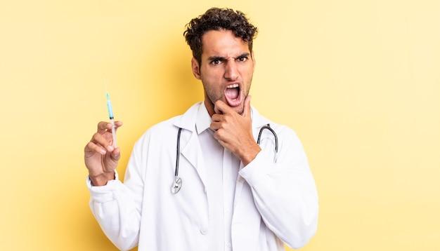 Bell'uomo ispanico con bocca e occhi spalancati e mano sul mento medico e concetto di srynge