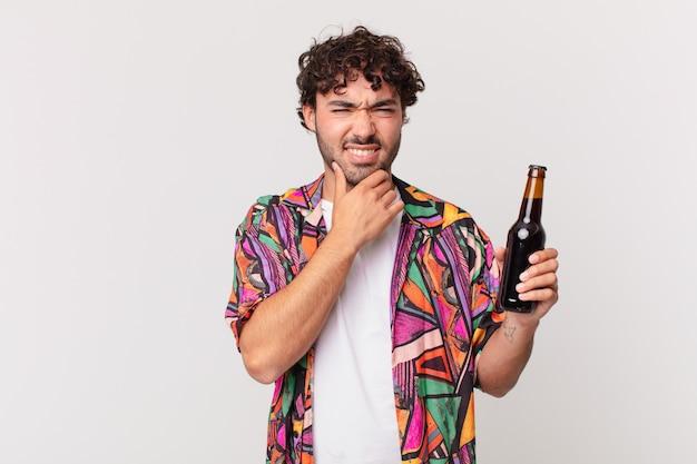 Uomo ispanico con birra con la bocca e gli occhi spalancati e la mano sul mento, sentendosi spiacevolmente scioccato, dicendo cosa o wow