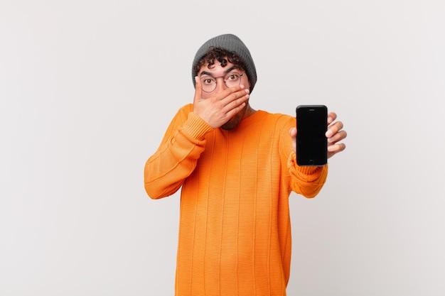Uomo ispanico con una cella che copre la bocca con le mani con un'espressione scioccata e sorpresa, mantenendo un segreto o dicendo oops