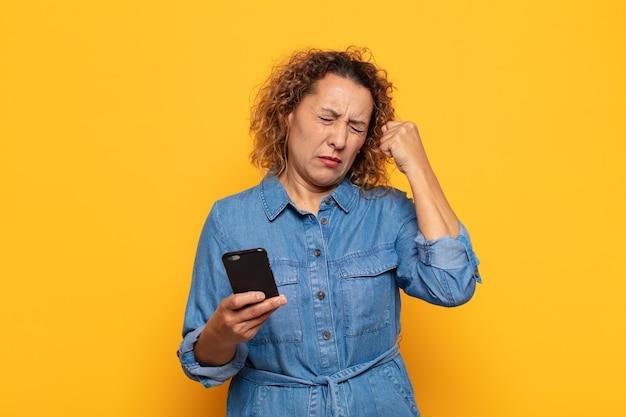 Donna ispanica di mezza età che sembra infelice e stressata, gesto di suicidio che fa il segno della pistola con la mano, indicando la testa