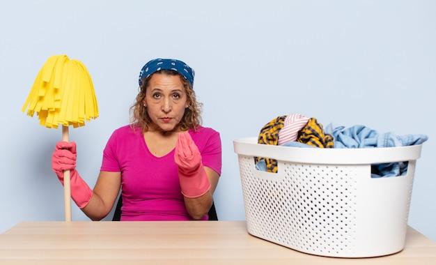 Donna ispanica di mezza età che fa capice o gesto di denaro, dicendoti di pagare i tuoi debiti!