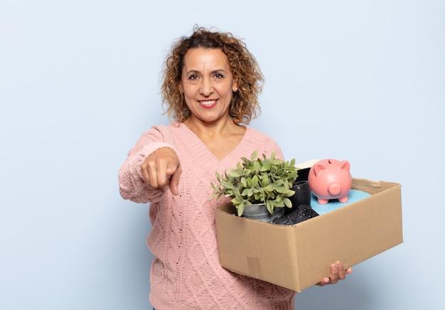 Donna ispanica di mezza età che punta alla telecamera con un sorriso soddisfatto, fiducioso, amichevole, scegliendo te