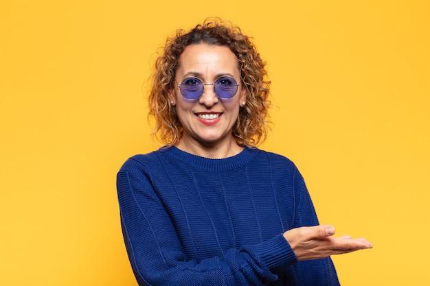 Donna ispanica di mezza età che sorride allegramente, sentendosi felice e mostrando un concetto nello spazio della copia con il palmo della mano