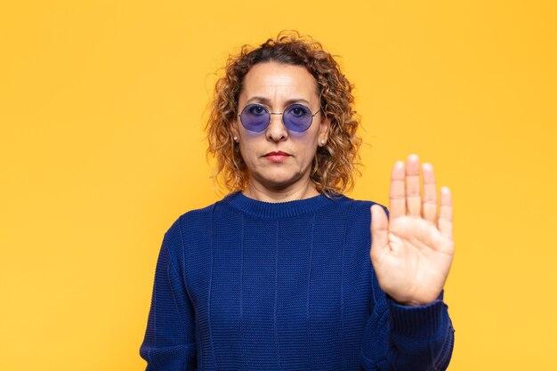 Ispanico donna di mezza età che sembra serio, severo, dispiaciuto e arrabbiato che mostra il palmo aperto che fa il gesto di arresto