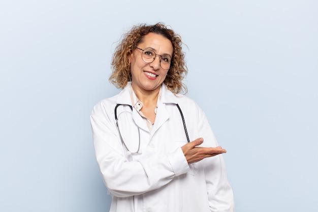 Ispanico donna di mezza età che sorride allegramente, sentendosi felice e mostrando un concetto nello spazio della copia con il palmo della mano