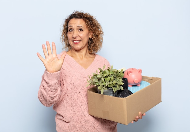 Ispanico donna di mezza età sorridente e guardando amichevole, mostrando il numero cinque o quinto con la mano in avanti, conto alla rovescia