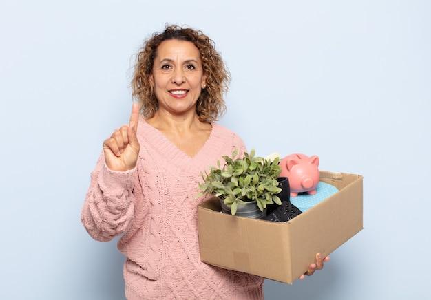 Ispanico donna di mezza età sorridente e guardando amichevole, mostrando il numero uno o il primo con la mano in avanti, conto alla rovescia