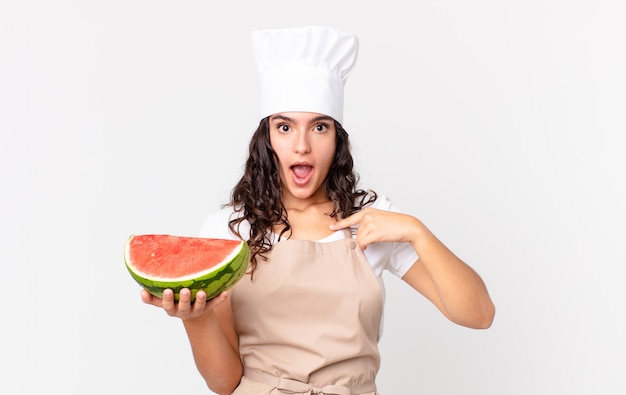 Bella donna ispanica chef che sembra scioccata e sorpresa con la bocca spalancata, che punta a se stessa e tiene in mano un cocomero