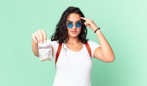 Bella donna ispanica che si sente confusa e perplessa, mostra che sei pazzo e tiene in mano un sacchetto di marijuana