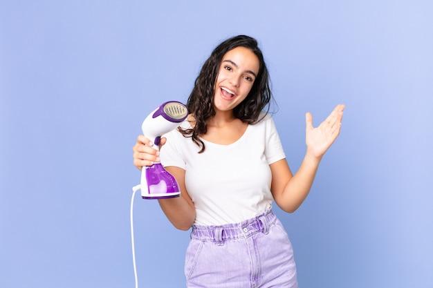 Bella donna ispanica che si sente felice, sorpresa nel realizzare una soluzione o un'idea e in possesso di un ferro da stiro a vapore