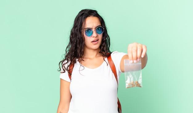 Bella donna ispanica che si sente perplessa e confusa e tiene in mano un sacchetto di marijuana