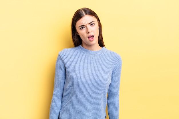Bella donna ispanica che si sente perplessa e confusa, con un'espressione stupida e sbalordita che guarda qualcosa di inaspettato
