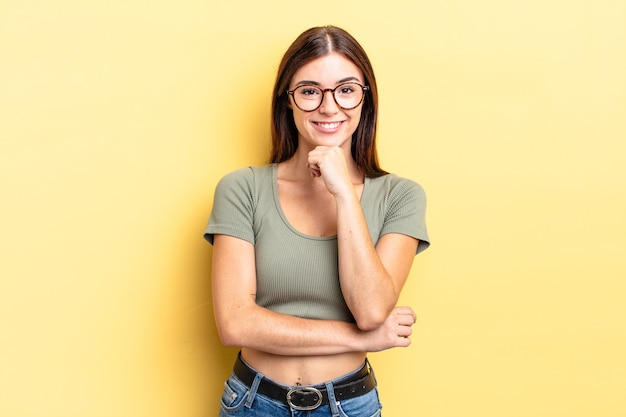 Bella donna ispanica che sembra felice e sorridente con la mano sul mento, chiedendosi o facendo una domanda, confrontando le opzioni