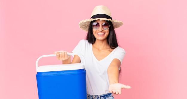 Bella donna ispanica che sorride felicemente con amichevole e offre e mostra un concetto con un frigorifero portatile da picnic