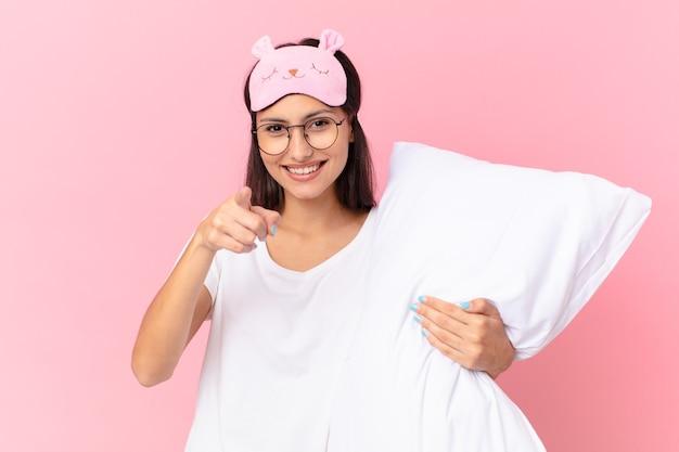 Bella donna ispanica che indossa un pigiama e tiene un cuscino