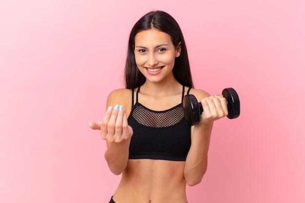 Bella donna ispanica con un manubrio. concetto di fitness