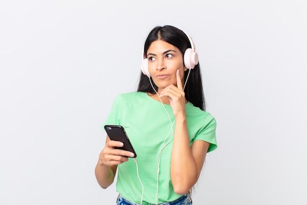 Bella donna ispanica con le cuffie e uno smartphone