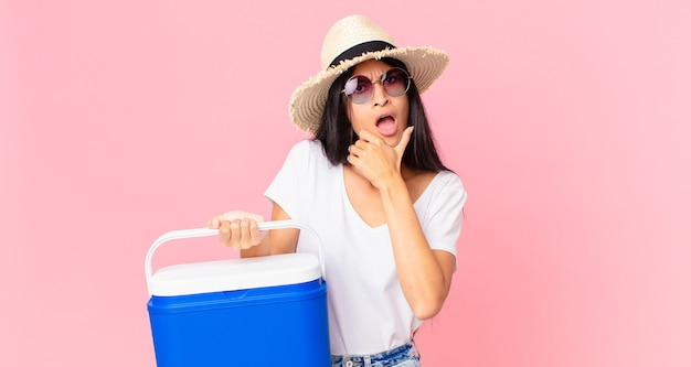 Bella donna ispanica con la bocca e gli occhi spalancati e la mano sul mento con un frigorifero portatile da picnic