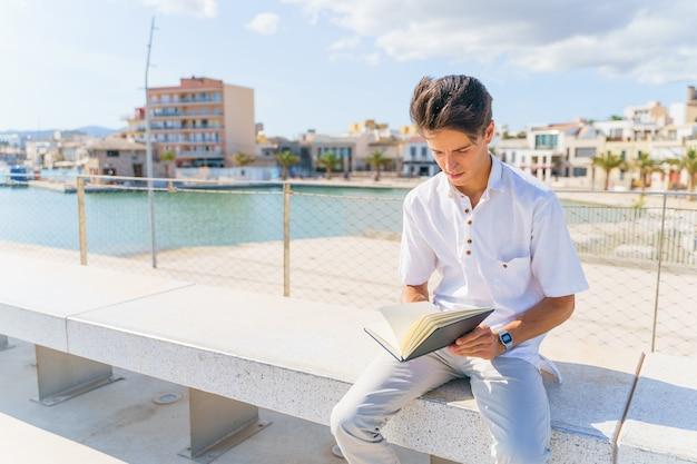 Studente ispanico seduto su una panchina e leggendo su un taccuino