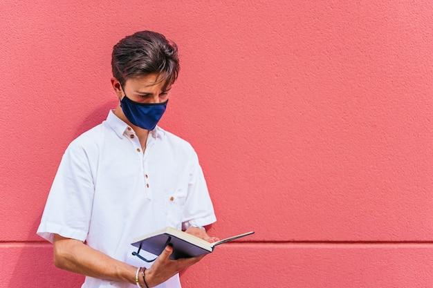 Studente ispanico in piedi su un muro rosso leggendo le note in un taccuino