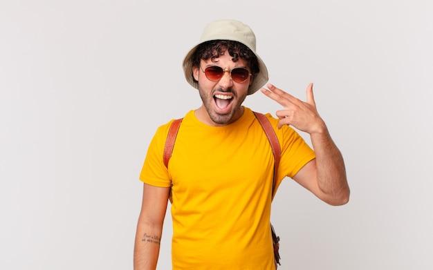 Uomo turistico ispanico che sembra infelice e stressato, gesto di suicidio che fa segno di pistola con la mano, indicando la testa